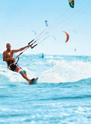 Recreational Sports. Man Kiteboarding In Sea Water. Extreme Spor
